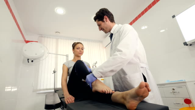 Aerial of a doctor exercising woman's legs video