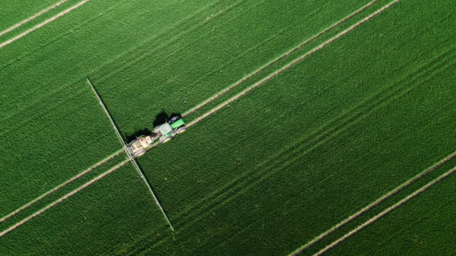 Aerial of a tractor spraying pesticides Flight directly above a tractor spraying fertilizer on an agricultural field. Aerial view. Shot in  North Rhine Westphalia, Germany monoculture stock videos & royalty-free footage