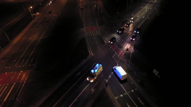 aerial-uttaget på ambulansen kör genom staden korsningen på natten - ultra high definition television bildbanksvideor och videomaterial från bakom kulisserna