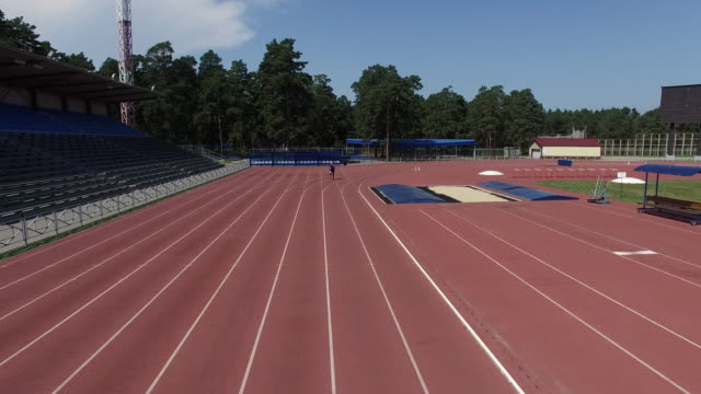 Aerial of amputee athlete running on track - vídeo