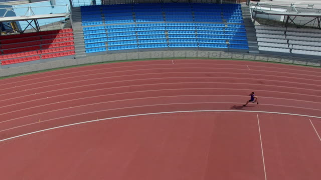 Aerial of amputee runner training at empty stadium Aerial view of amputee athlete with prosthetic leg running on track at empty outdoor stadium artificial limb stock videos & royalty-free footage