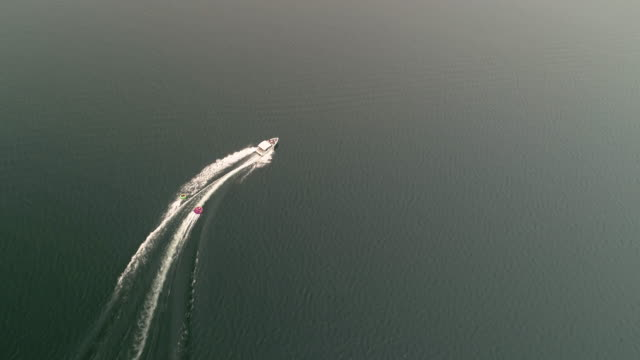 Aerial of Boat Pulling Inner Tubes into Smoke from Forest Fire video