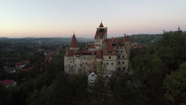 vídeos de stock e filmes b-roll de aerial of bran castle on a hill near bran village - castle
