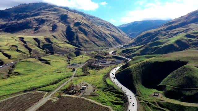 aerial of california grapevine and interstate 5 freeway farmland - paesaggio collinare video stock e b–roll