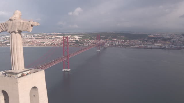 Aerial of Christ the King monument and 25 de Abril Bridge Aerial view of Christ the King monument and 25 de Abril Bridge, Lisbon. ponte 25 de abril stock videos & royalty-free footage