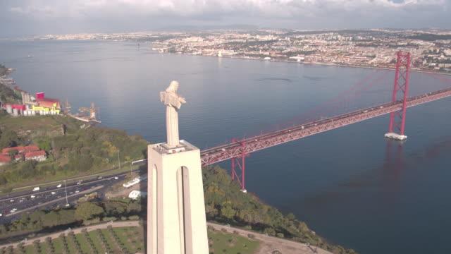 vídeos de stock e filmes b-roll de aerial of christ the king sanctuary and 25 de abril bridge - ponte 25 de abril