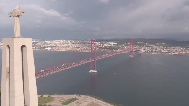 Aerial of Christ the King statue and 25 de Abril Bridge Aerial view of Christ the King statue and 25 de Abril Bridge, Lisbon. ponte 25 de abril stock videos & royalty-free footage