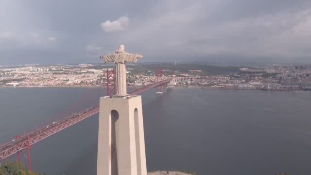Aerial of Christ the King statue and 25 de Abril Bridge Aerial of Christ the King statue and 25 de Abril Bridge, in Lisbon. ponte 25 de abril stock videos & royalty-free footage
