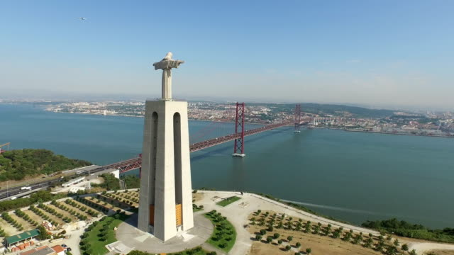 Aerial of Christ the King statue and 25th of April bridge Aerial view of Christ the King statue and 25th of April bridge in Lisbon. cristo redentor stock videos & royalty-free footage