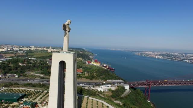 vídeos de stock e filmes b-roll de aerial of christ the king statue near 25th of april bridge - ponte 25 de abril