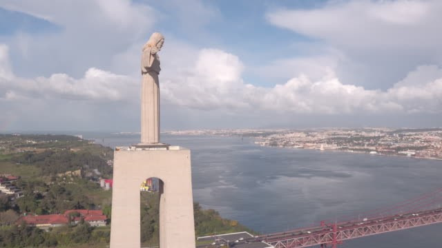 Aerial of Christ the King statue on Tagus riverside Aerial view of Christ the King statue on Tagus riverside. ponte 25 de abril stock videos & royalty-free footage