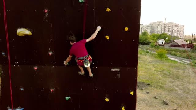 luftbild des kletterers läuft die geschwindigkeit klettern track auf künstliche wand im freien. junge sportler schneller klettert die klippe bei wettbewerben. mann auf sichern kabelbaum führt beim bouldern meisterschaft - bouldering stock-videos und b-roll-filmmaterial