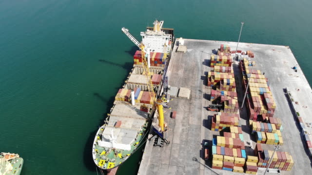 Aerial of container ship loading at dock. Drone shot of containers stacked on dock loaded by  cargo crane into docked ship at international trade port for export at harbor. construction machinery stock videos & royalty-free footage