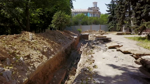 aerial of dug trenches for pipelines and communications at a construction site. water pipeline reconstruction and groundwork in the city. quadcopter 4k footage - cavo d'acciaio video stock e b–roll