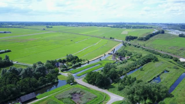 Aerial of Dutch landscape farmland with windmill and train travels along Dutch windmill in farmland area and a Nederlandse Spoorwegen (NS) train travelling along netherlands stock videos & royalty-free footage