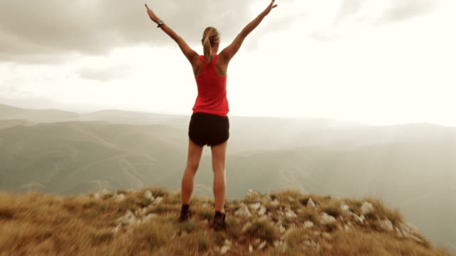 Aerial of female runner with raised hands on mountain top video
