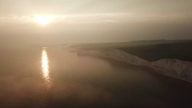 Aerial of foggy Seven Sisters Cliffs coast landscape in England at sunset
