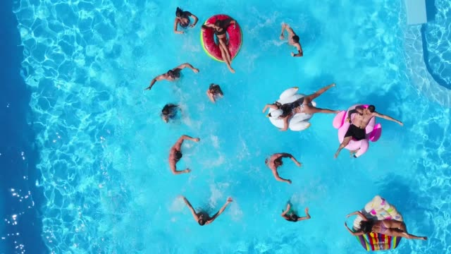 Aerial of friends having party in swimming pool with inflatable flamingo, swan, mattress, ring. Happy young people splashing water at resort on sunny day. View from above. Girls in bikini bathing