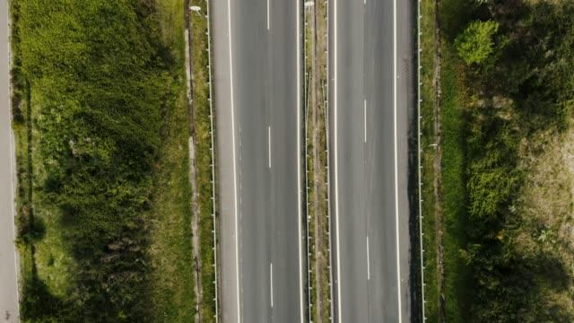 aerial of green countryside and highway - droga wielopasmowa filmów i materiałów b-roll