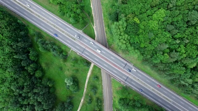 Aerial of Highway and Railroad Crossing Surrounded by Woods