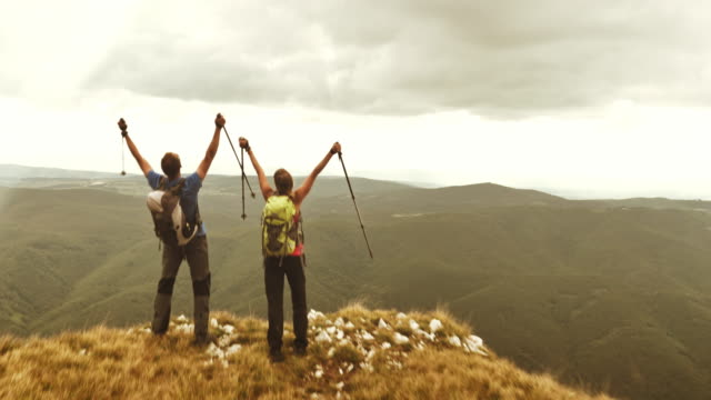 Aerial of hiking couple raising hands at mountain top video