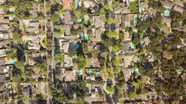 aerial of houses and trees in residential neighborhood - пригород стоковые видео и кадры b-roll