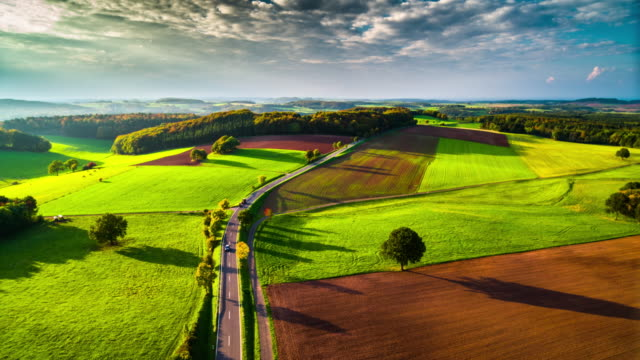 Aerial of idyllic countryside in Germany Flight over idyllic rural landscape in Germany. Country road leading through agricultural fields. Warm evening light hilights the topography of the landscape.  Eifel mountain range in North Rhine Westphalia, Germany. country road stock videos & royalty-free footage