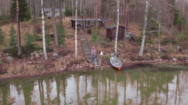 aerial of man stående på finland lake shore moor boat finsk stuga i bakgrunden - drone helsinki bildbanksvideor och videomaterial från bakom kulisserna
