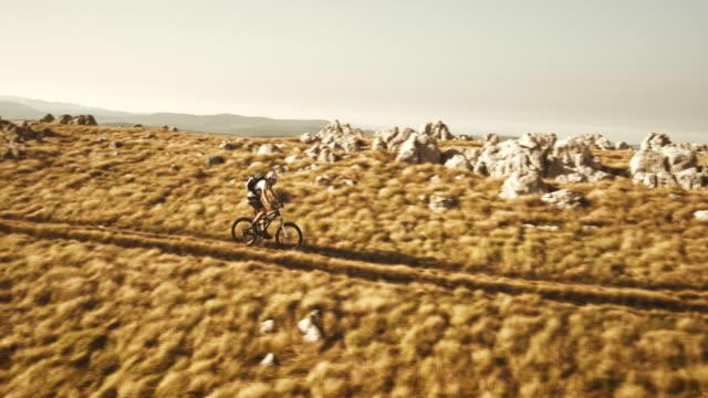 Aerial of mountain biker descending the grassy ridge video