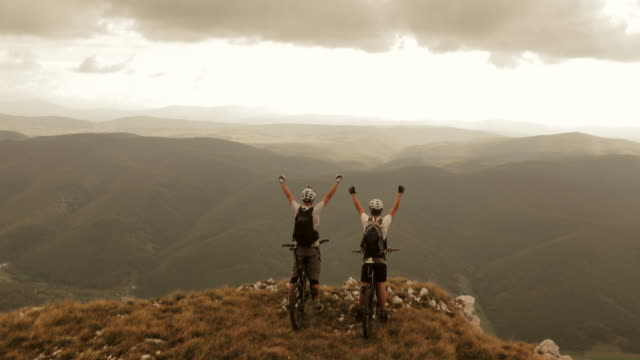 Aerial of mountain bikers on the ridge with raised hands video