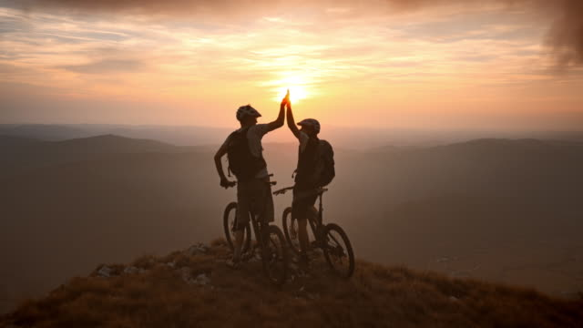 veduta aerea di ciclisti di mountain bike in cima al tramonto - in cima video stock e b–roll
