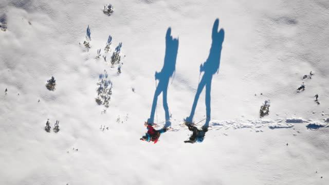 Aerial of mountaineers and their silhouettes snowshoeing on sunny day video