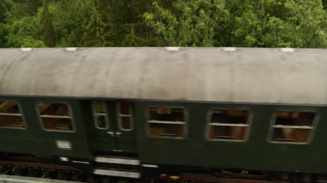 Aerial of old steam train on a trestle from above looking down
