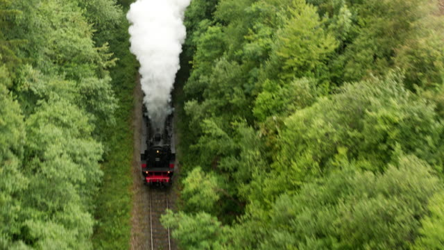 Aerial of old steam train with billowing smoke stack from the front