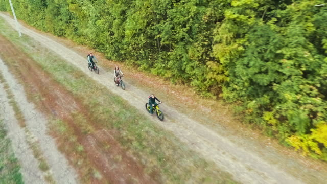 Aerial of parents and child biking along forest video