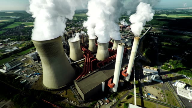 Aerial of Power Station Aerial shot of a coal fired power station with large chimneys and cooling towers. Camera flying to the left. coal stock videos & royalty-free footage
