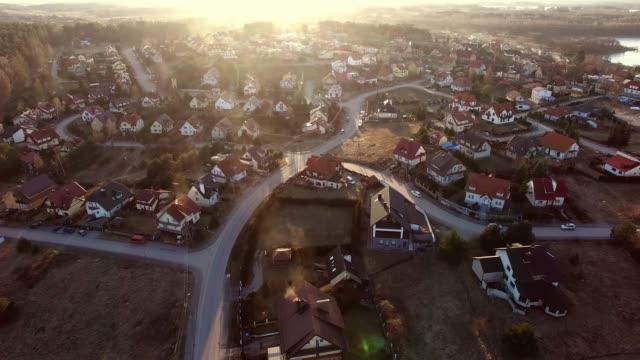 aerial of residential neighborhood and houses at sunset - polska filmów i materiałów b-roll