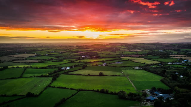 Aerial of rural landscape with fields and farmland under dramatic sunset sky, Ireland video