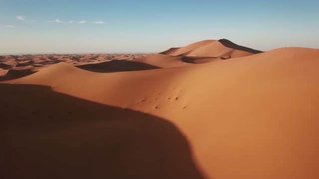 aerial of sand dunes in sahara desert at sunrise - desert stock videos & royalty-free footage