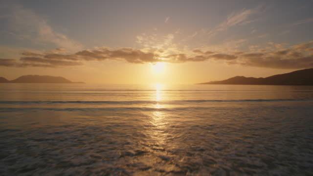 vídeos de stock e filmes b-roll de aerial of sea waves moving towards beach shore during sunset - linha do horizonte sobre água