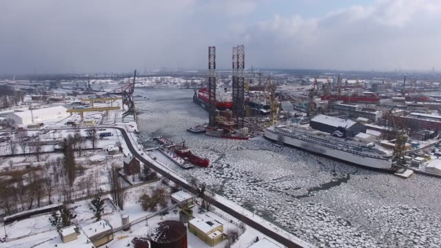 aerial of shipyard on frozen river with ice floes in winter - attrezzatura industriale video stock e b–roll