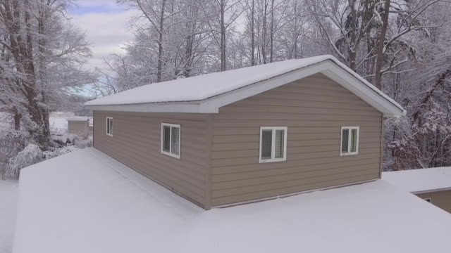 aerial of snow covered house climbing to view - dow jones industrial average video stock e b–roll