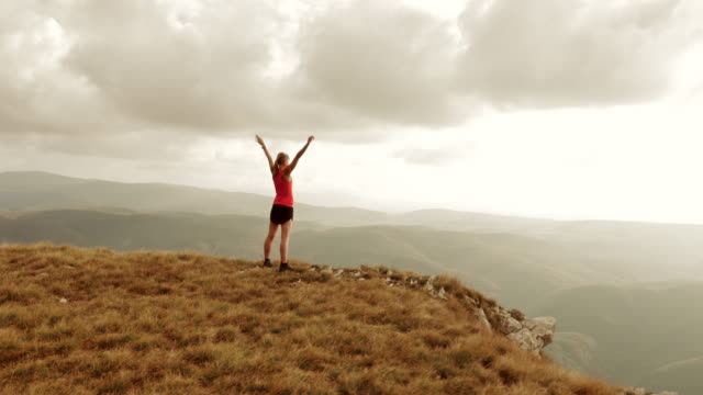 Aerial of sportswoman standing on mountain ridge with raised hands video