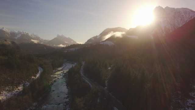 Aerial of Sunrise Lens Flare Above Snowy Mountain Valley with Road and Raging River video