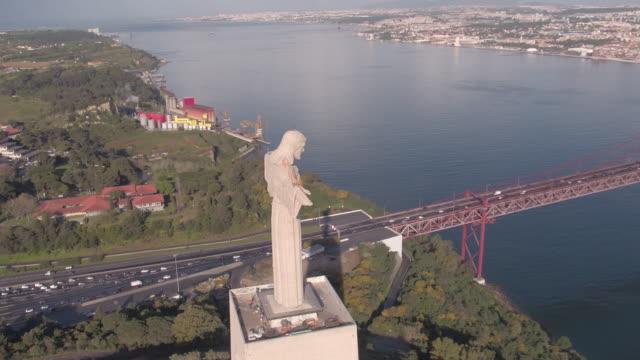 vídeos de stock e filmes b-roll de aerial of the christ monument near 25 de abril bridge - ponte 25 de abril