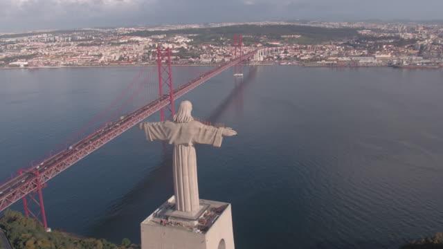 vídeos de stock e filmes b-roll de aerial of the christ statue near 25 de abril bridge - ponte 25 de abril
