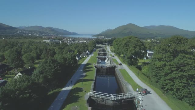 aerial of the neptune's staircase series of locks on the caledonian canal in banavie tilting down past the pleasure boats in fort william, scotland - fort william video stock e b–roll