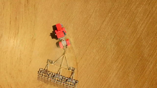 Aerial of tractor on harvest field Aerial of tractor on harvest field harrow agricultural equipment stock videos & royalty-free footage
