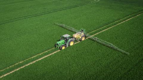 antenna del trattore che spruzza pesticidi su un campo agricolo - agricoltura video stock e b–roll