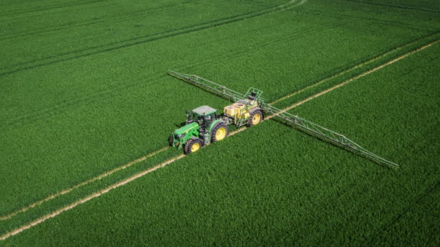 Aerial of Tractor spraying pesticides on an agricultural field Aerial shot of a tractor towing an applicator spraying liquid fertilizer on a corn field. Shot in  North Rhine Westphalia, Germany cultivated land stock videos & royalty-free footage